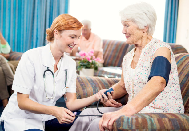 caregiver checking blood pressure of the elderly woman