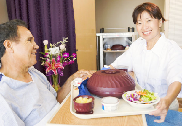 caregiver preparing meal for elderly man