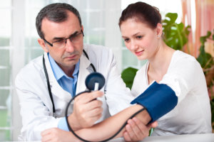 doctor checking blood pressure of the woman