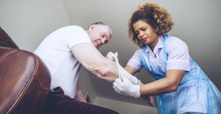 caregiver putting arm cover on the elderly man's arm